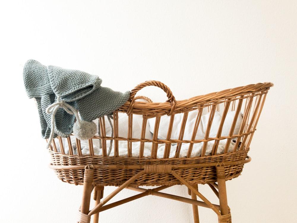 茶色の籐のバスケットに掛かっている灰色の繊維