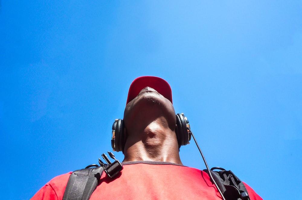 man looking up while wearing black headphones