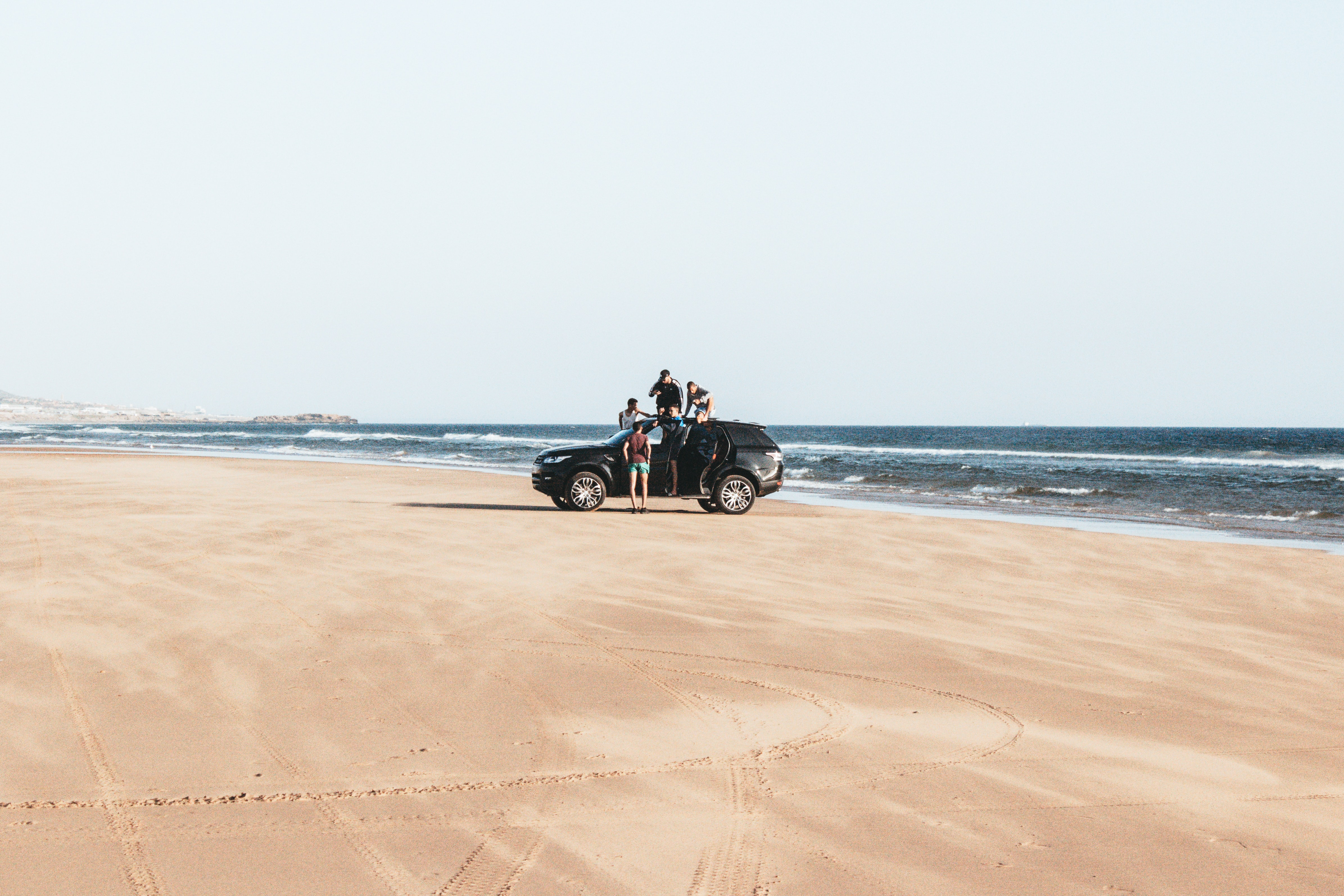 black vehicle parked on shore with four men during daytime