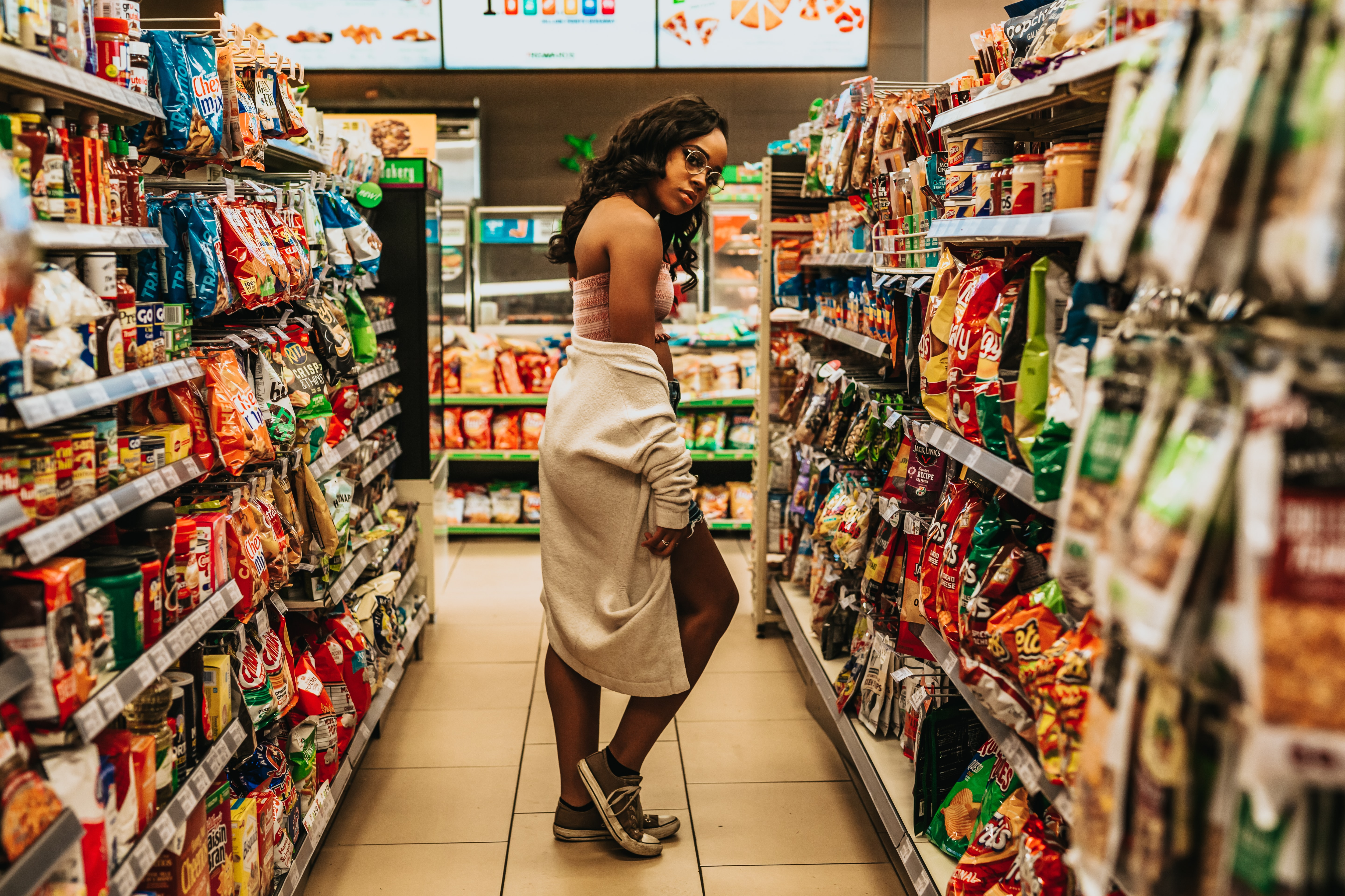 woman posing between store shelves with products in store interior