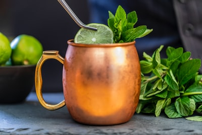 brass-colored mug with sliced lime pot of gold teams background