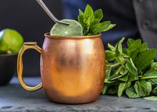 brass-colored mug with sliced lime