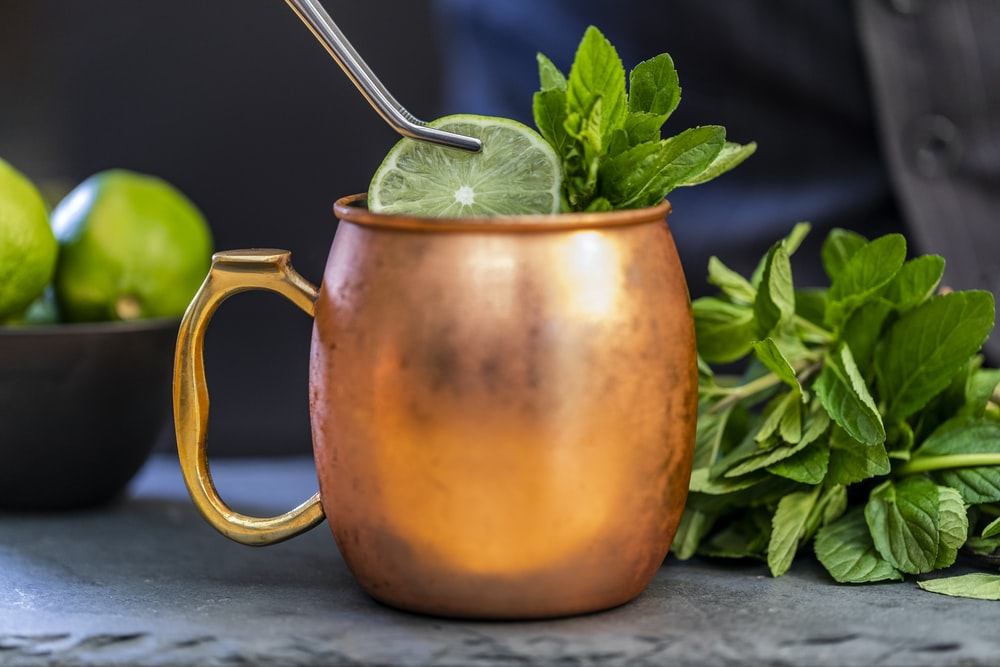 brass-colored mug with sliced lime