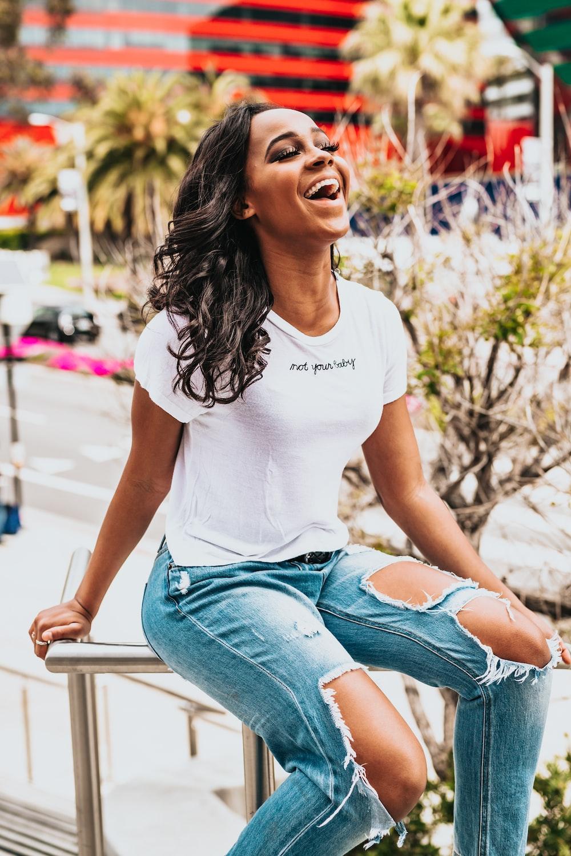 girl sitting on metal hand rail while laughing