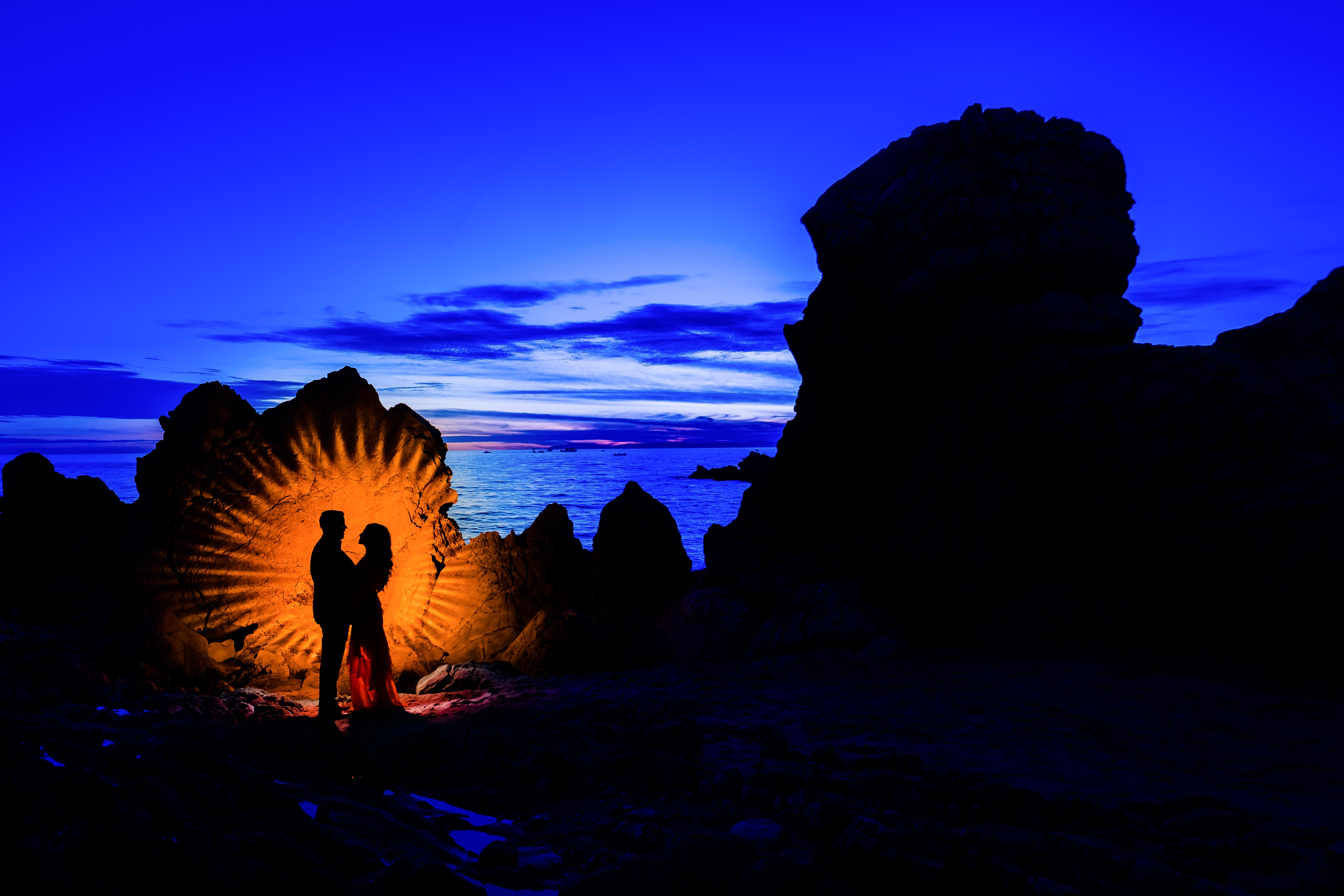 man and woman standing near rock formation near sea in silhouette photography