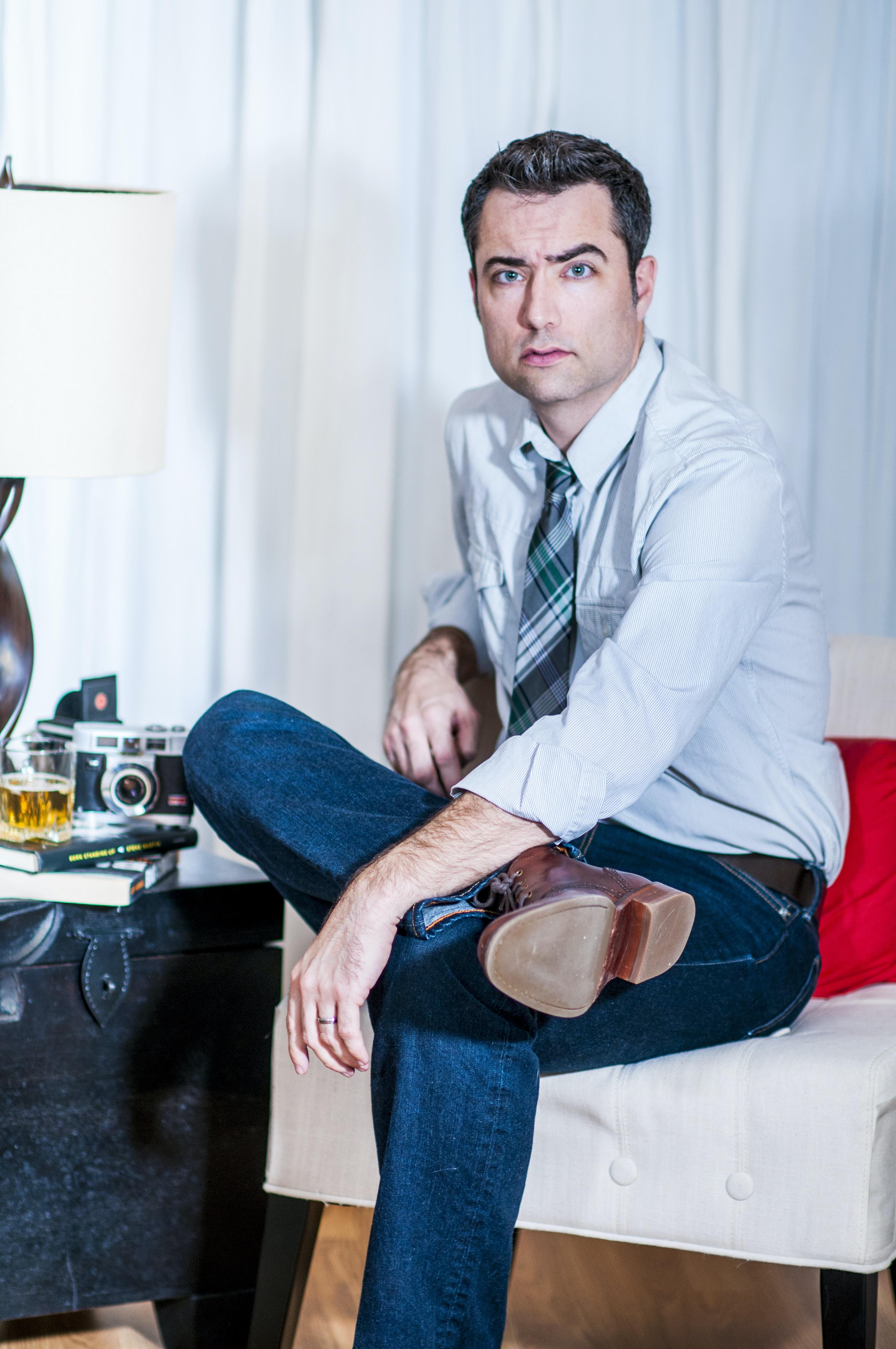 man cross-legged sitting on padded sofa chair