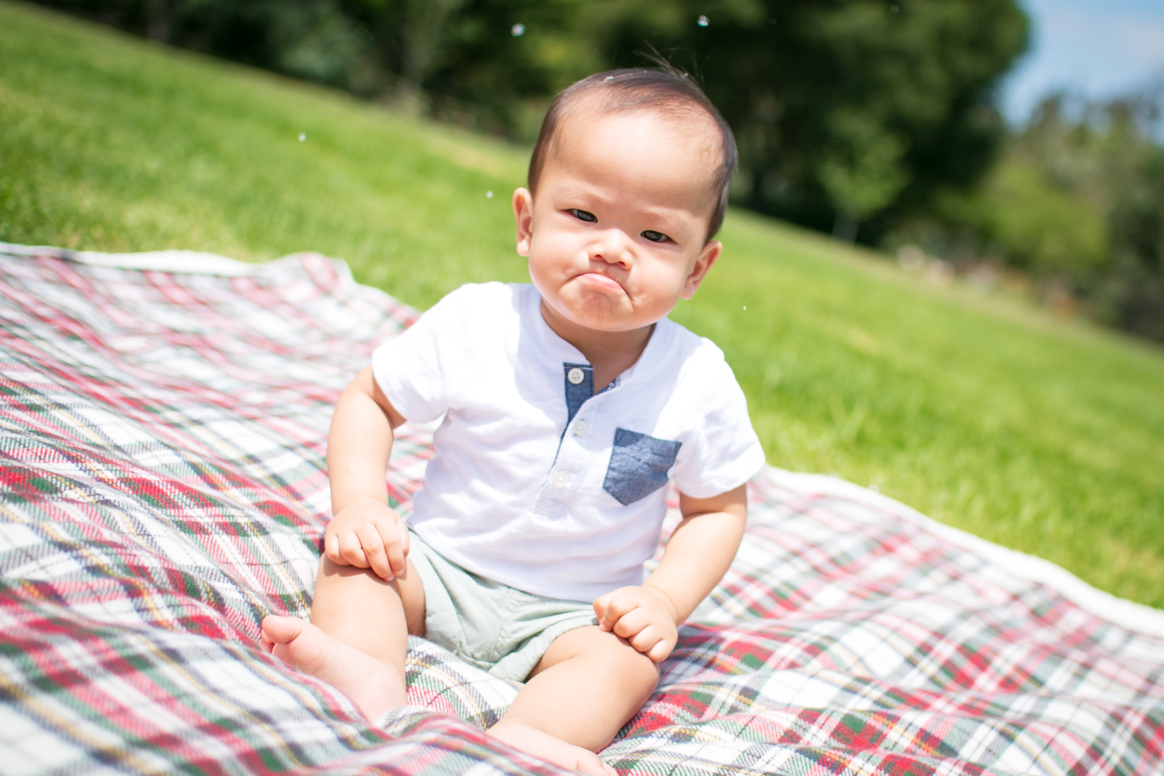 selective focus photography of grumpy face toddler sitting on plaid pad taken during daytime