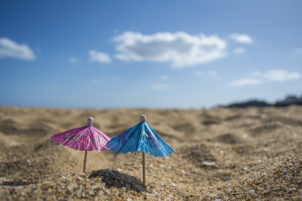 shallow focus photography of cocktail umbrellas pin down in sand