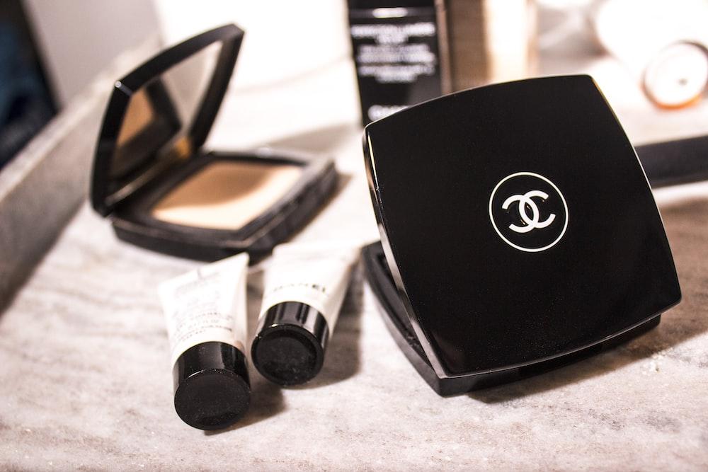 women's Chanel pressed powder beside tube bottles