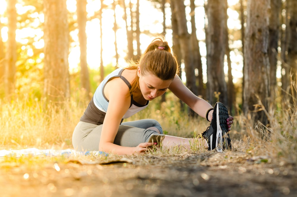 woman doing stretching near trees