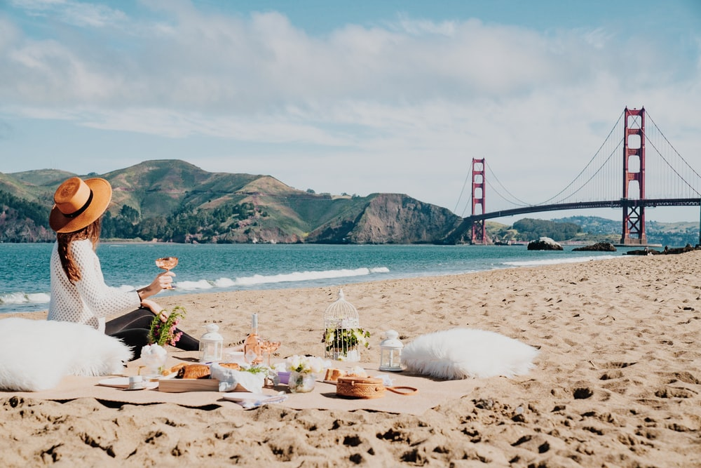 woman sitting near seashore while looking at Golden Gate, Sam Francisco