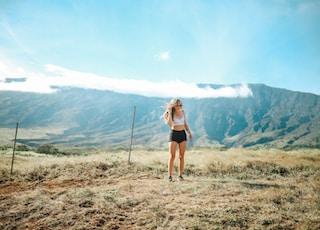woman standing on grass field near posts