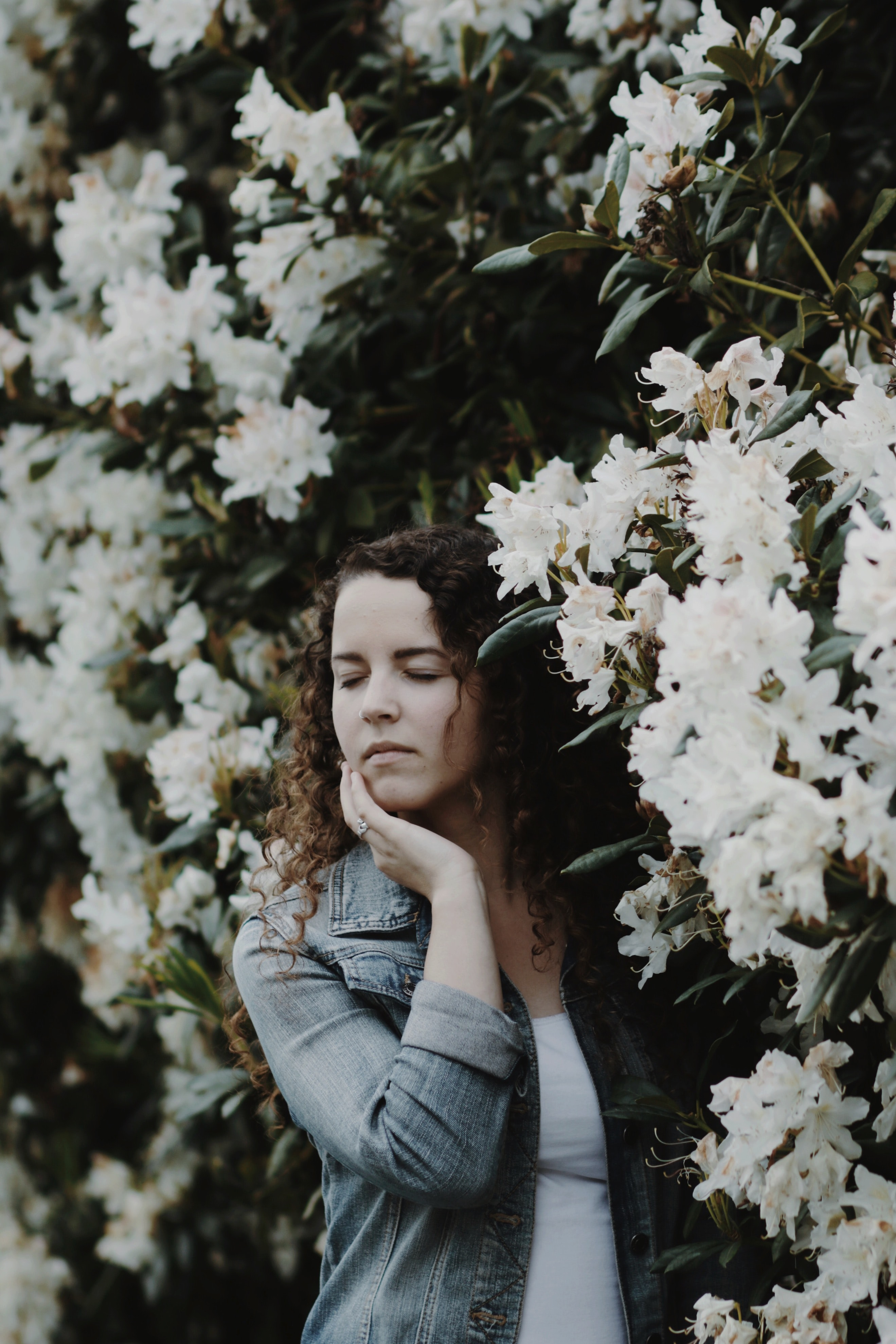 woman touching face with her right hand with white flowers on background