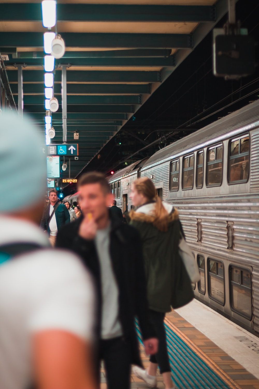 people standing on train station near train during nighttime