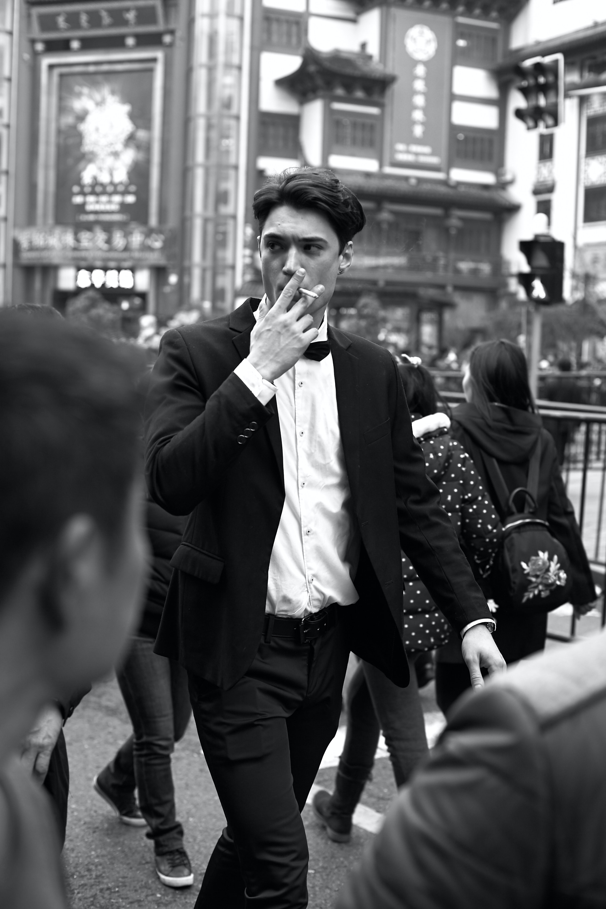 man walking while smoking grayscale photography