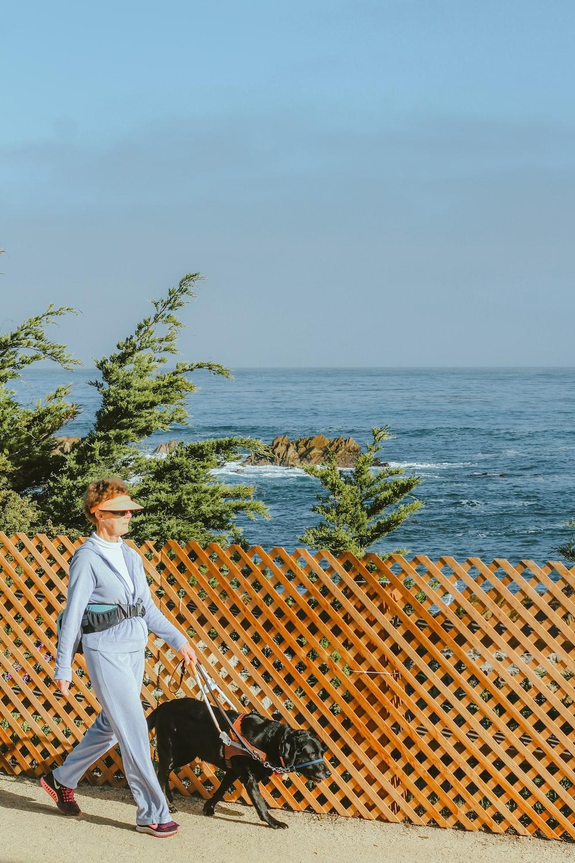 woman with dog walking beside lattice fence