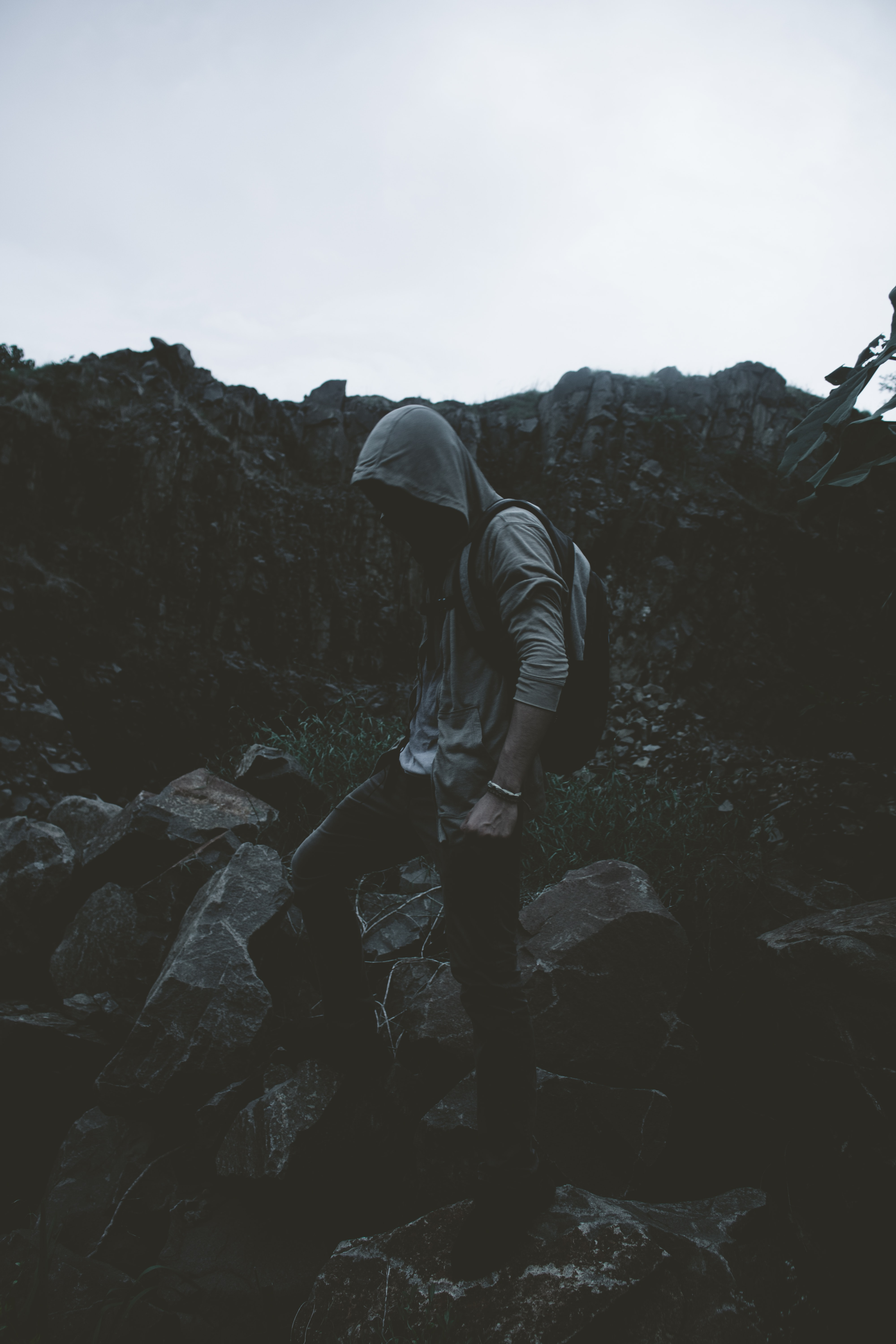 man in hoodie stepping on rocks