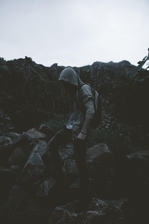man in hoodie stepping on rocks