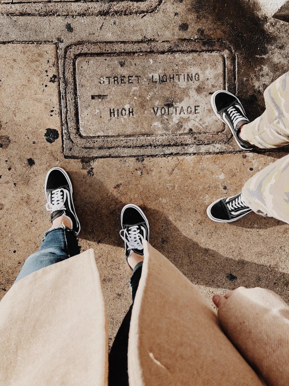 two person wearing pair of black Vans Old Skool low-top sneakers
