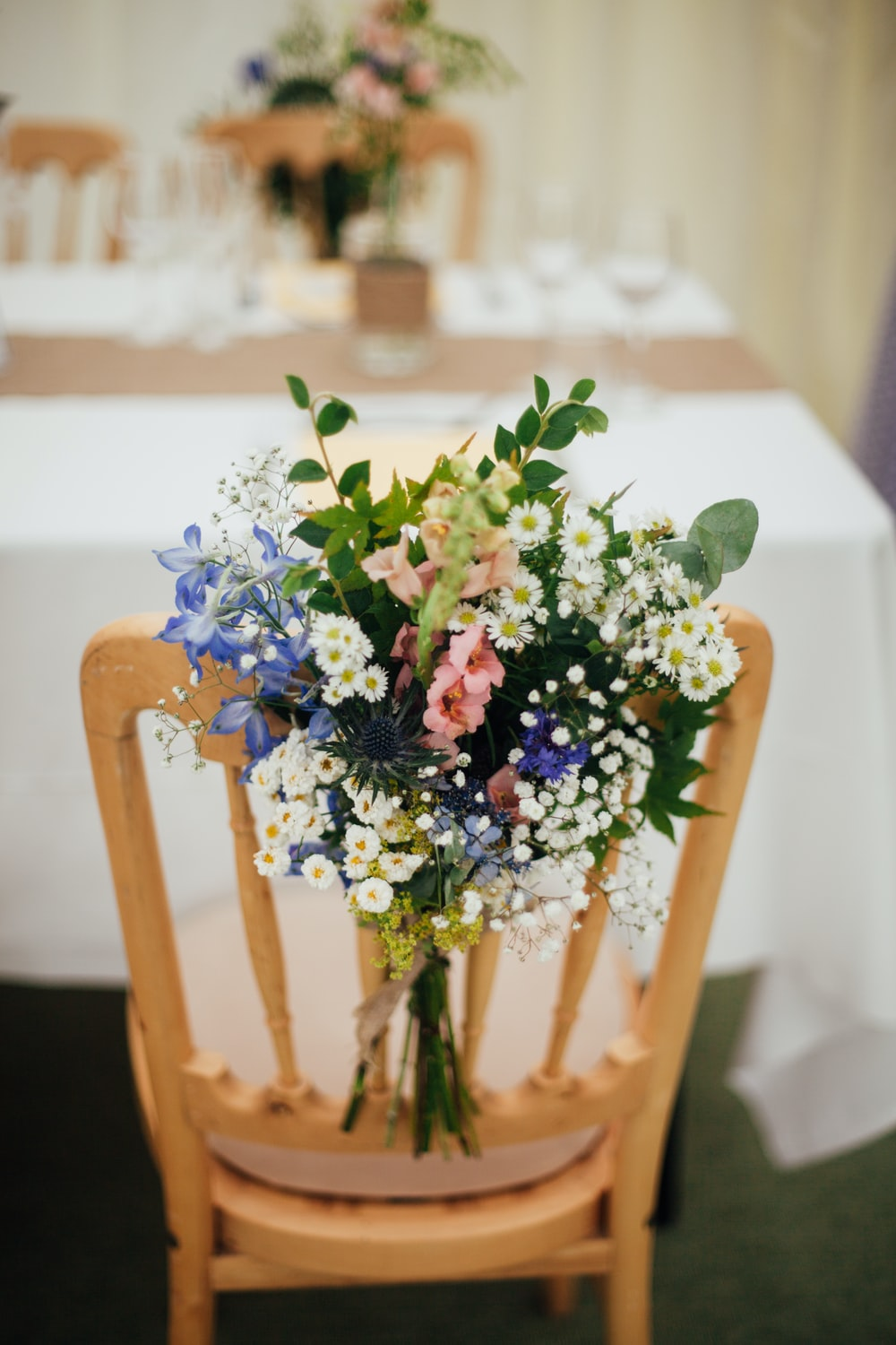 white petaled flowers on brown wooden armless chair