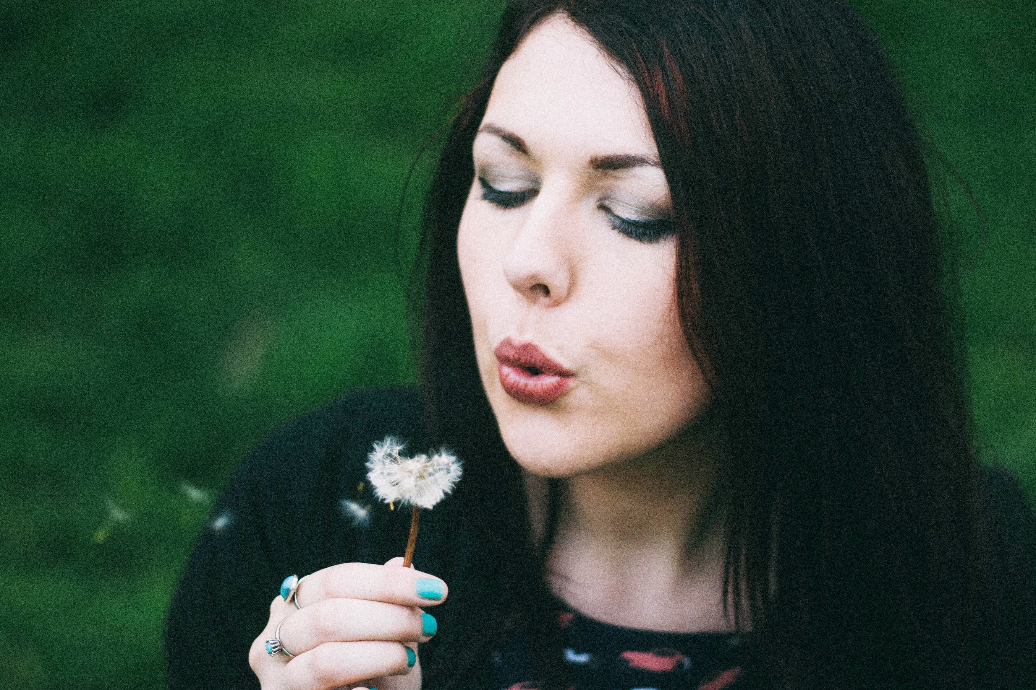 woman blowing white dandelion