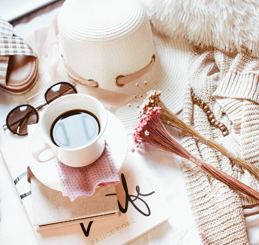 white ceramic mug filled with coffee near brown jacket