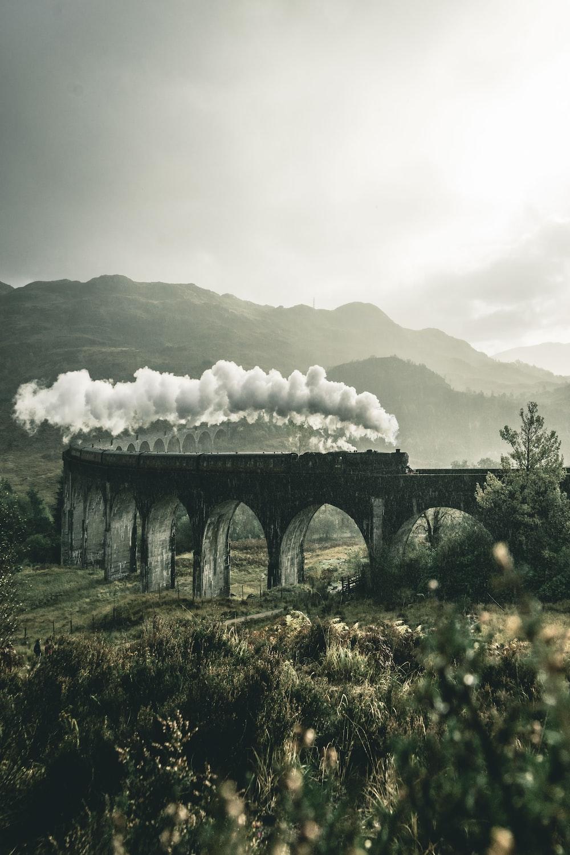 black train on railway bridge under heavy clouds