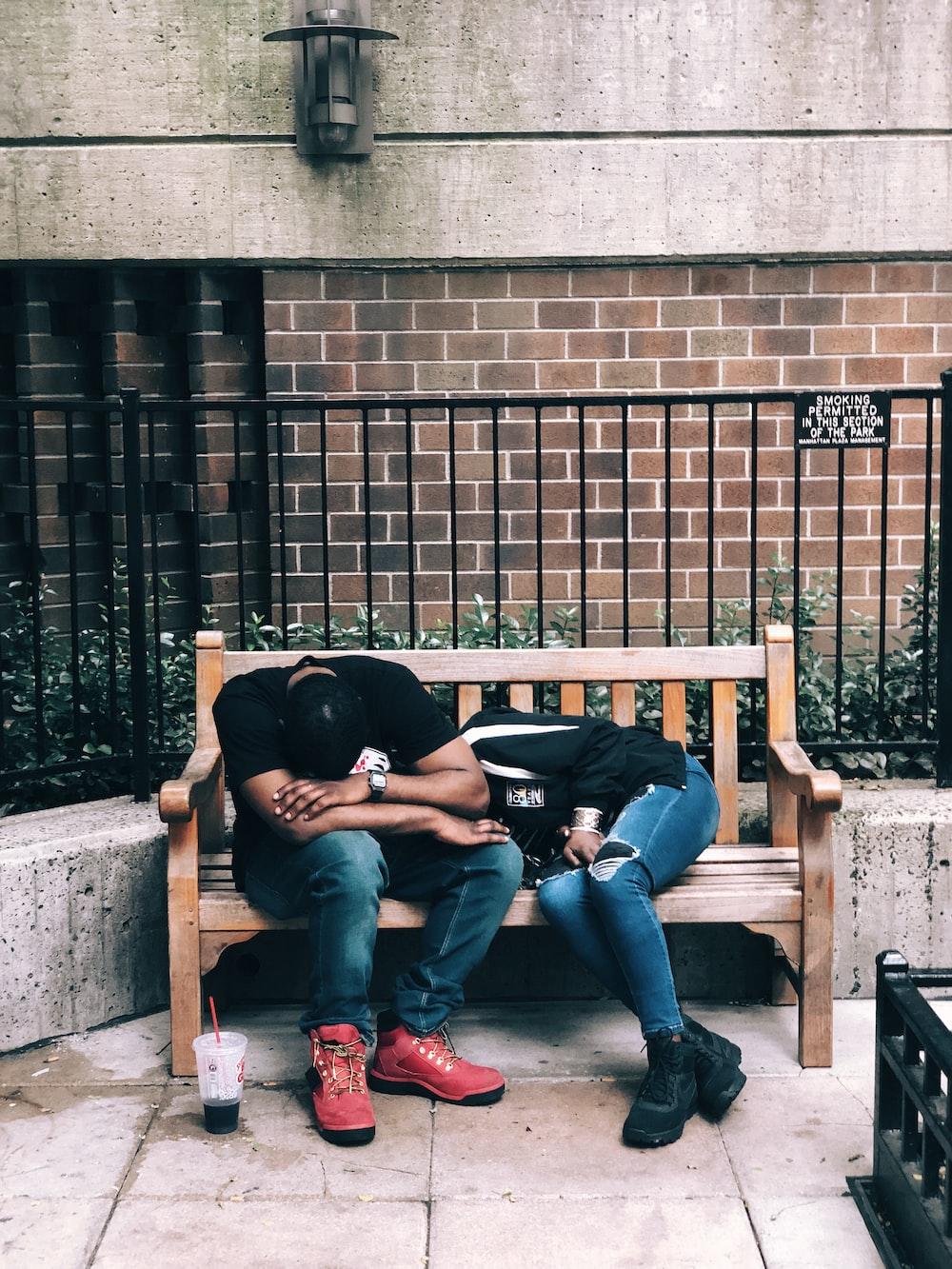 man sitting on bench beside lying woman