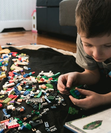 boy in grey crew-neck t-shirt plays LEGO bricks with white manual book