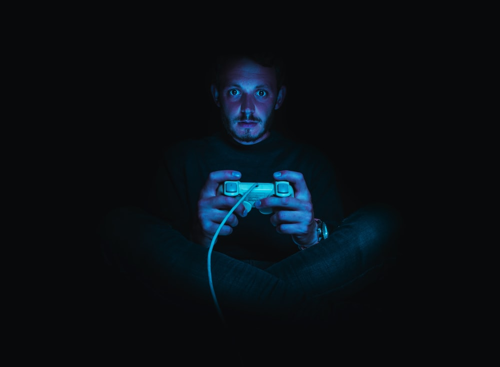 man holding corded game controller