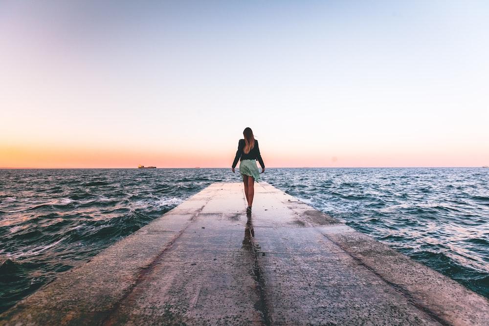 woman walking near dock wooder during daytime