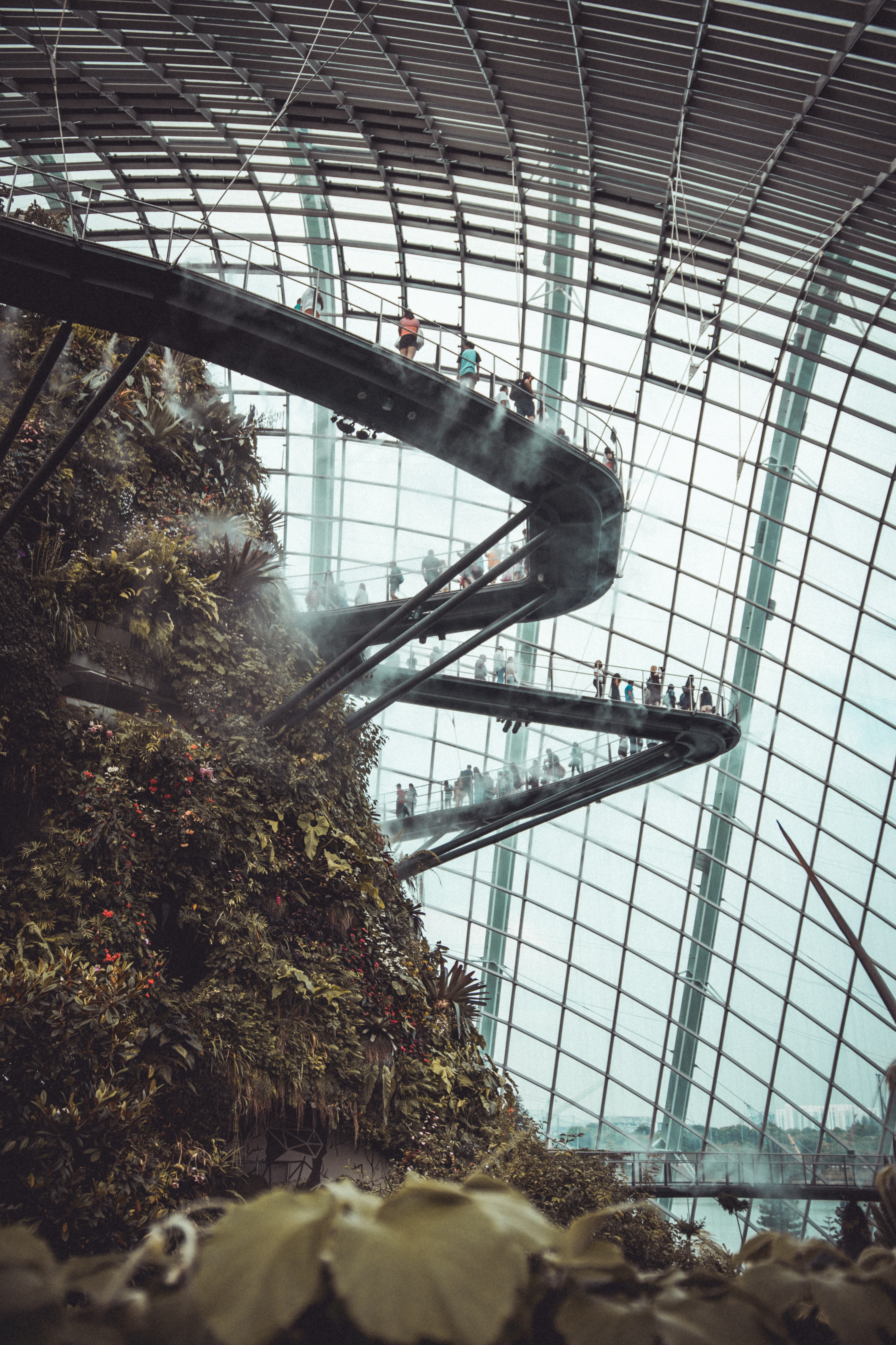 person inside a glass dome on a huge mound with stairs