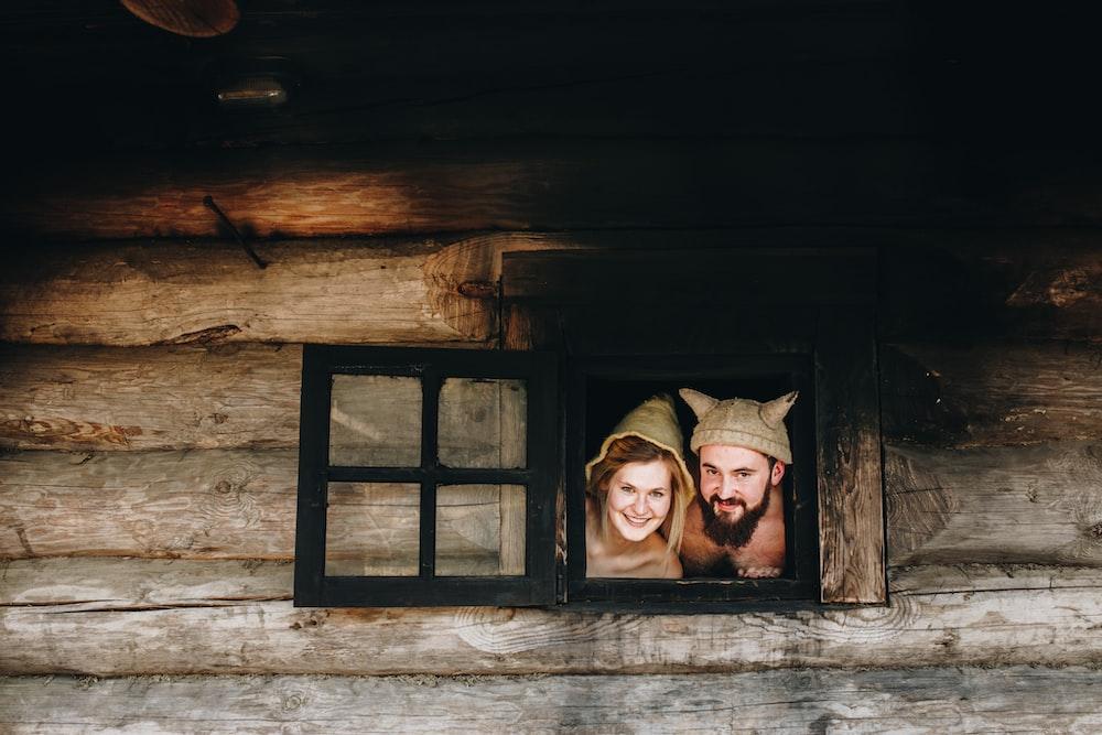 man and woman peeking on window
