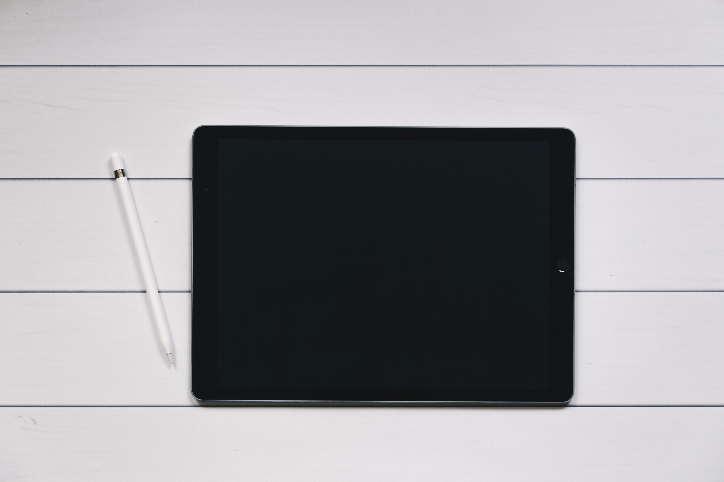 space gray iPad with Apple Pencil with white and black pinstriped background
