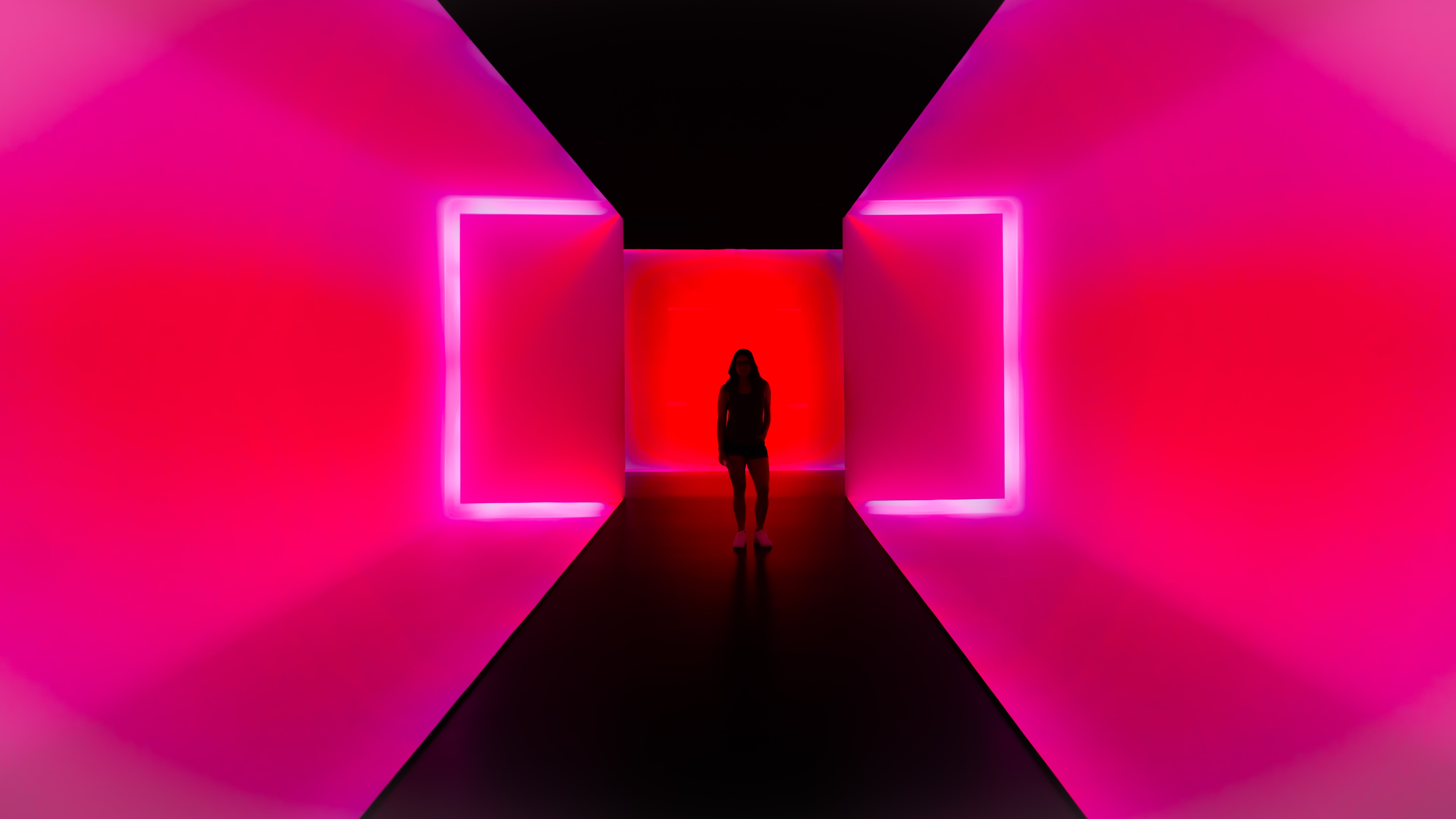 attention grabbing image of female model silhouetted on bright pink neon background