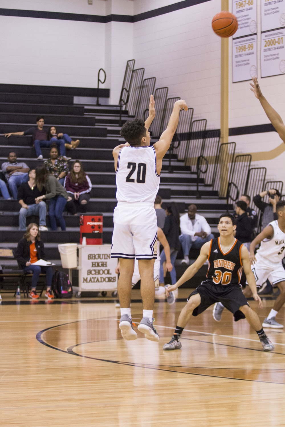 man in white and black number 20 jersey shirt shooting a basketball