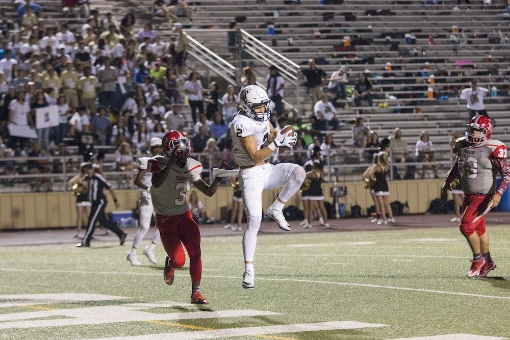 man catching brown football on stadium