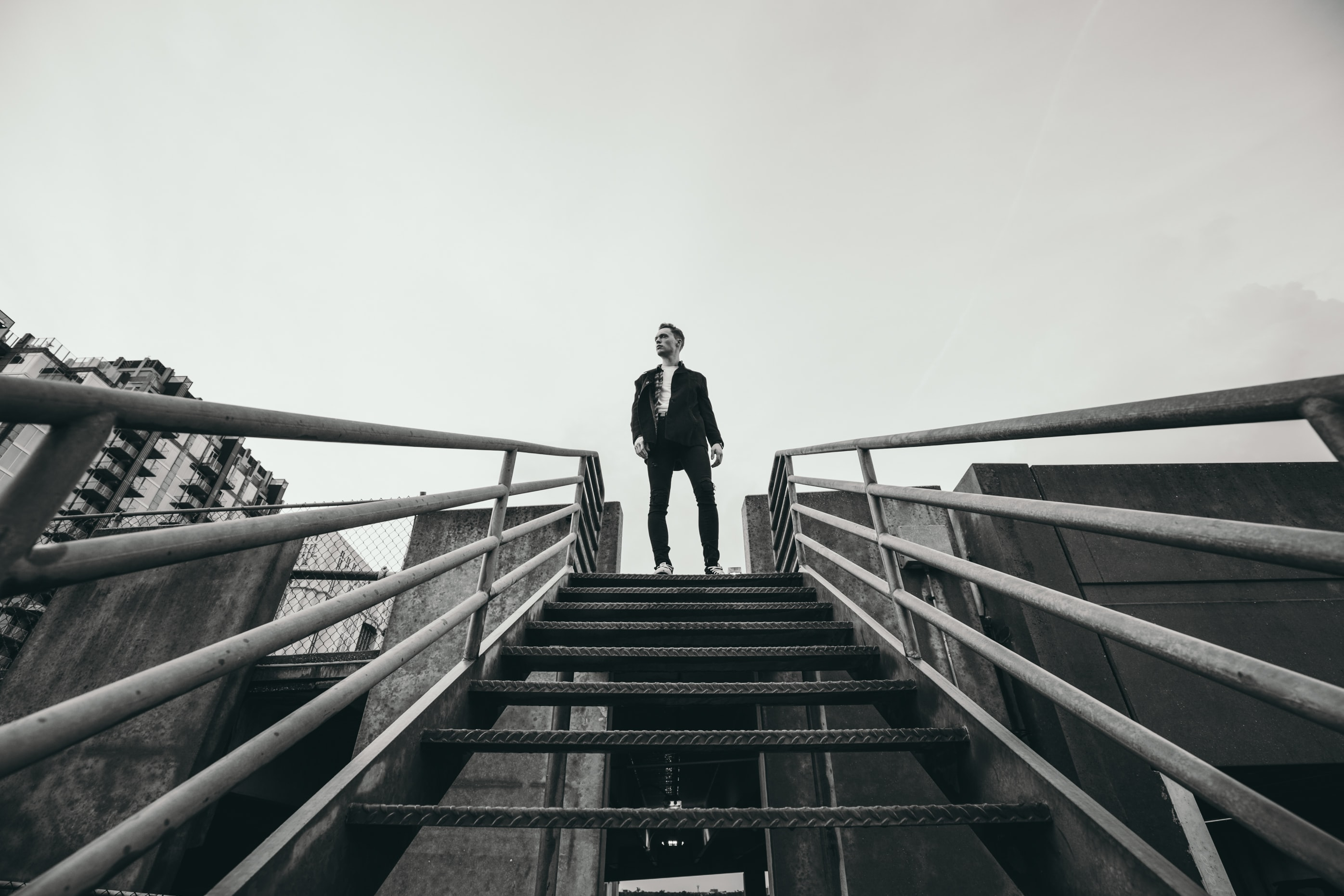 grayscale photo of man standing at the edge of the stairs