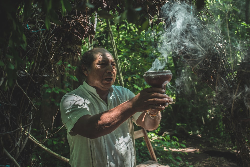 man holding brown pot with smoke
