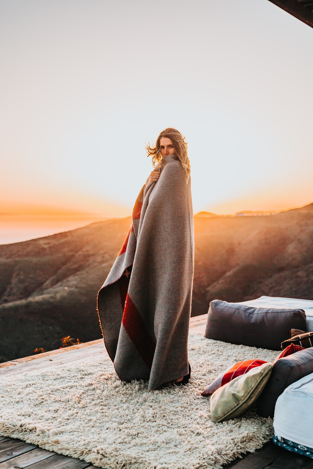 woman covered by gray comforter