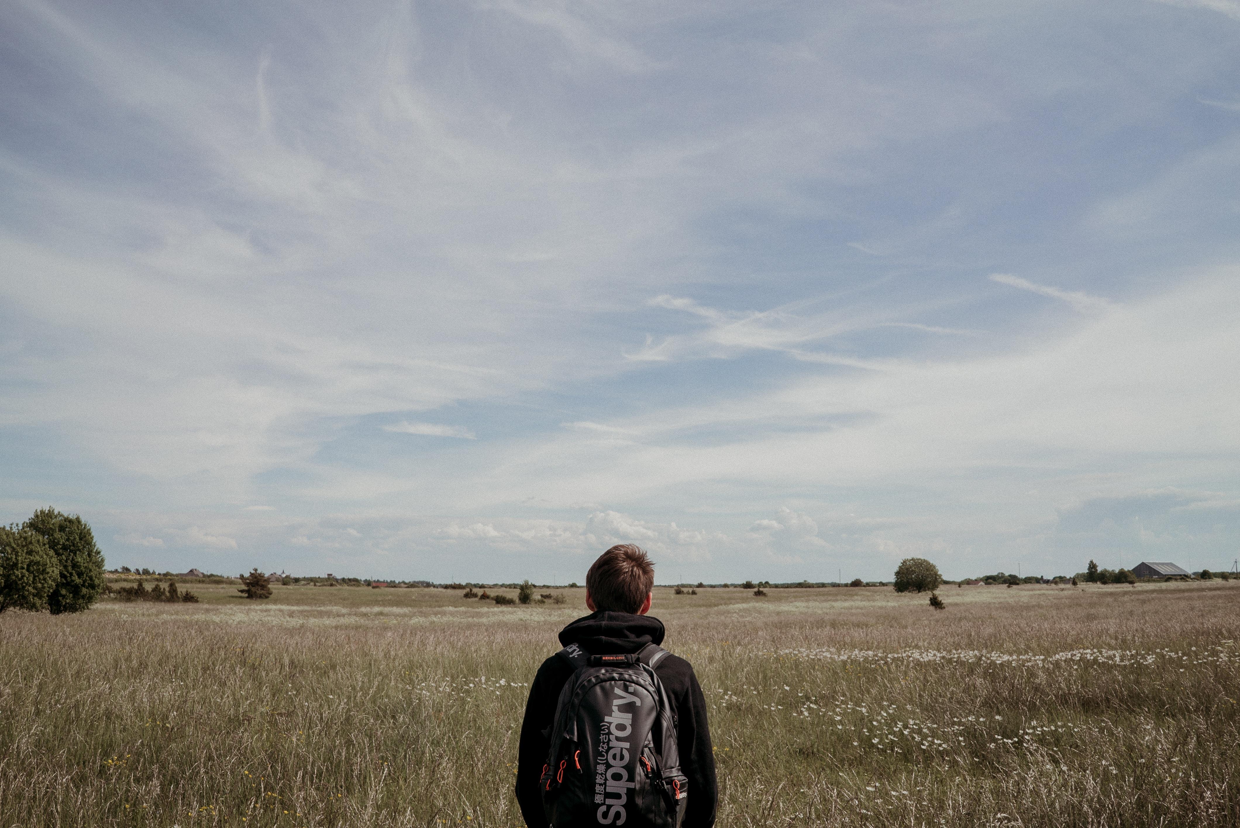 man standing on brown grass field under cloudy sky