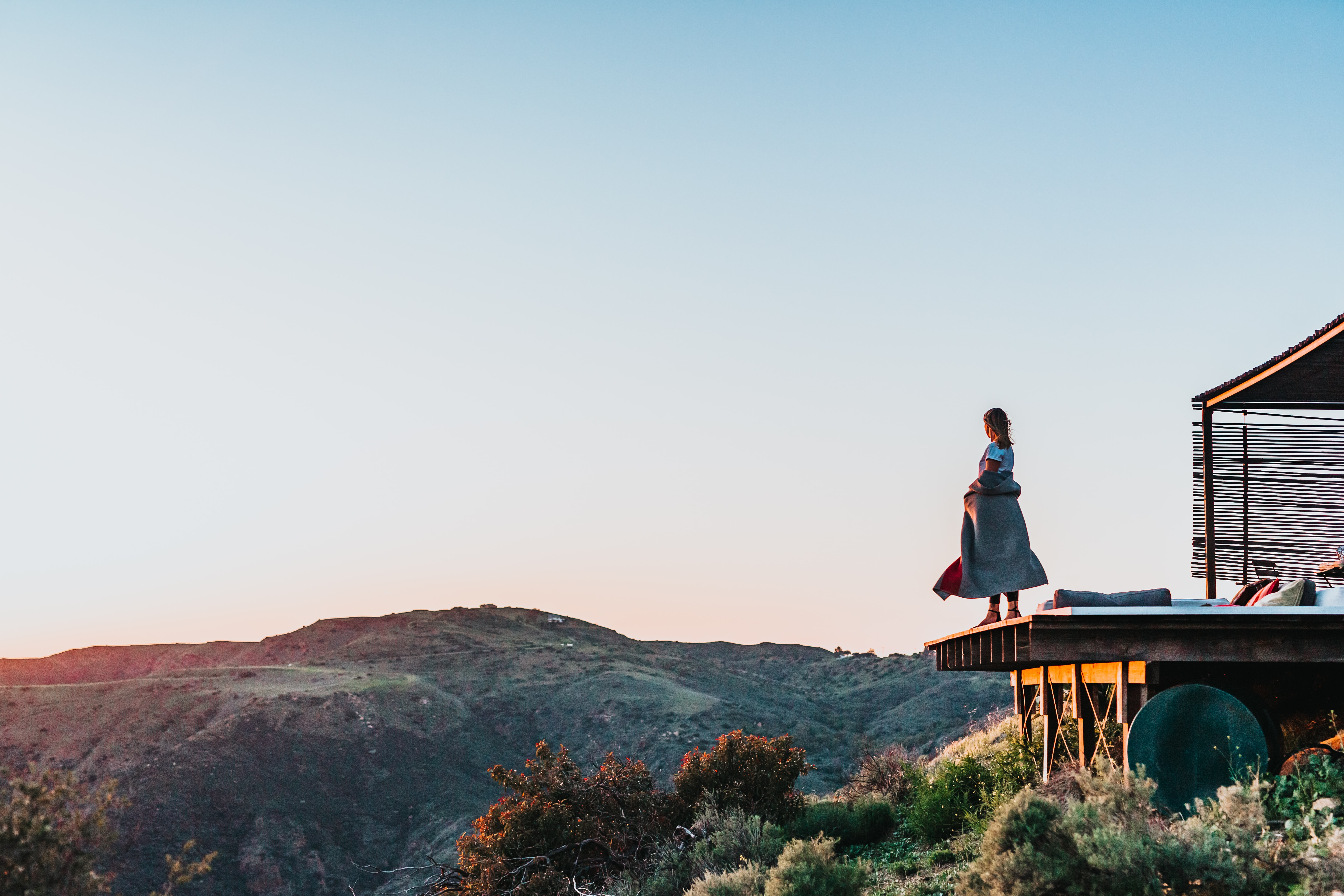 woman standing on brown wooden platform near mountain during daytime