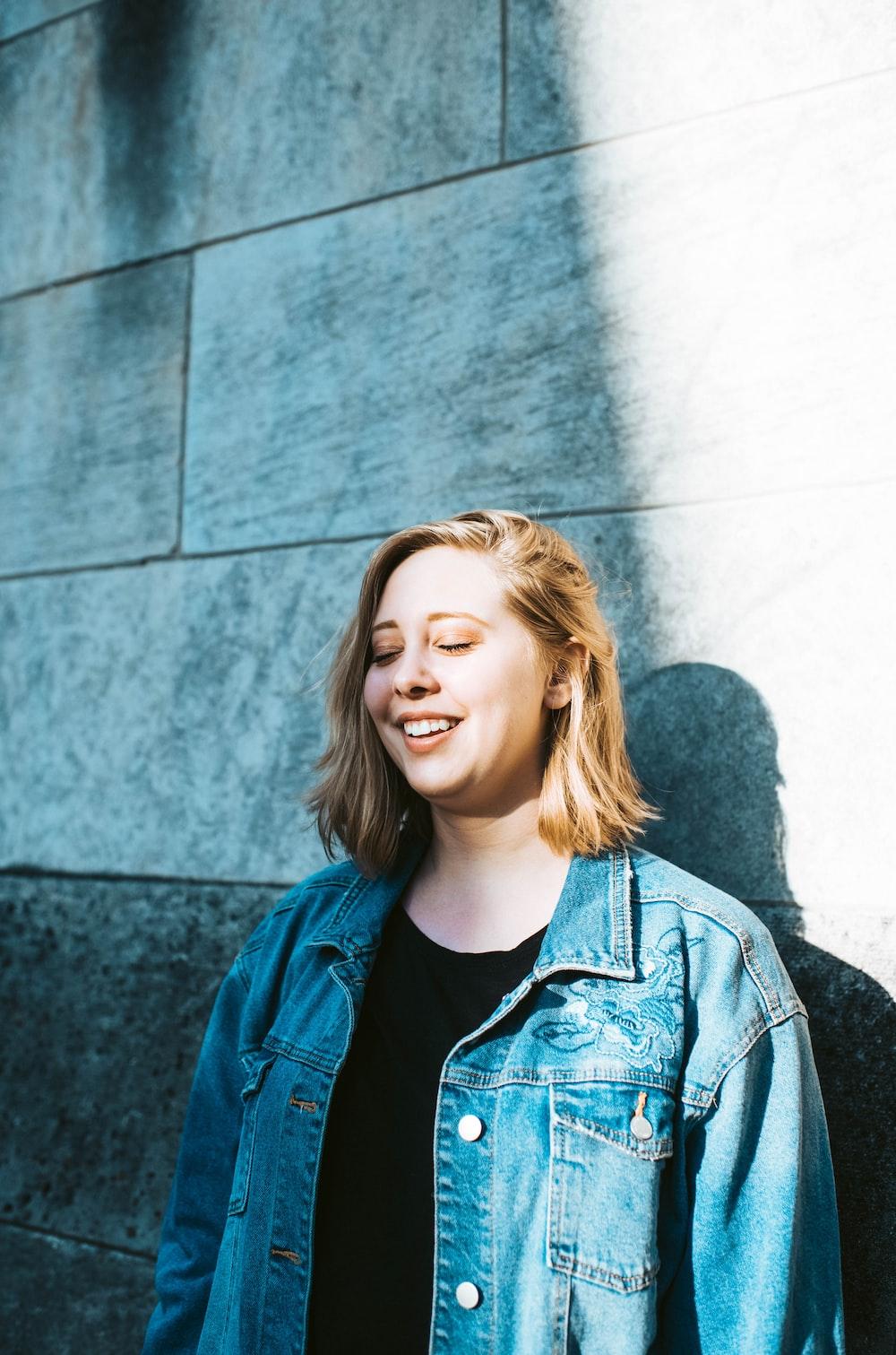 woman in blue denim jacket leaning on wall