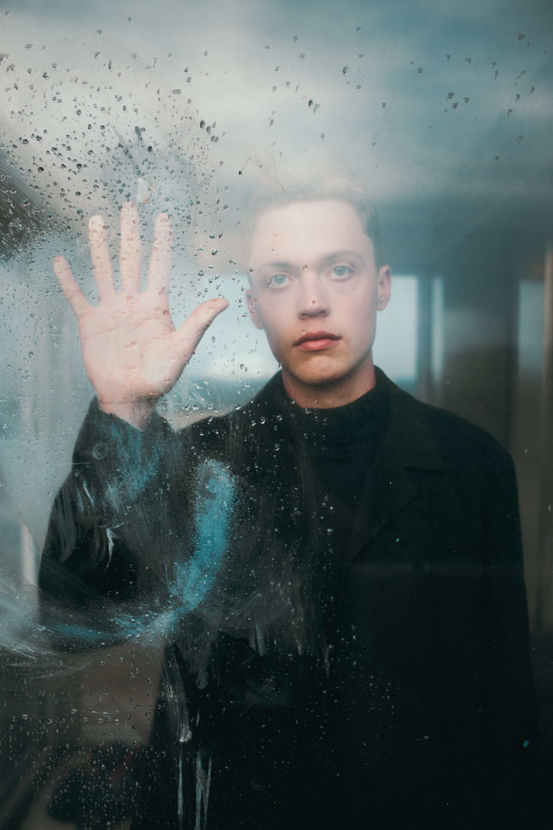 man standing in front of glass wall while touching it during daytime