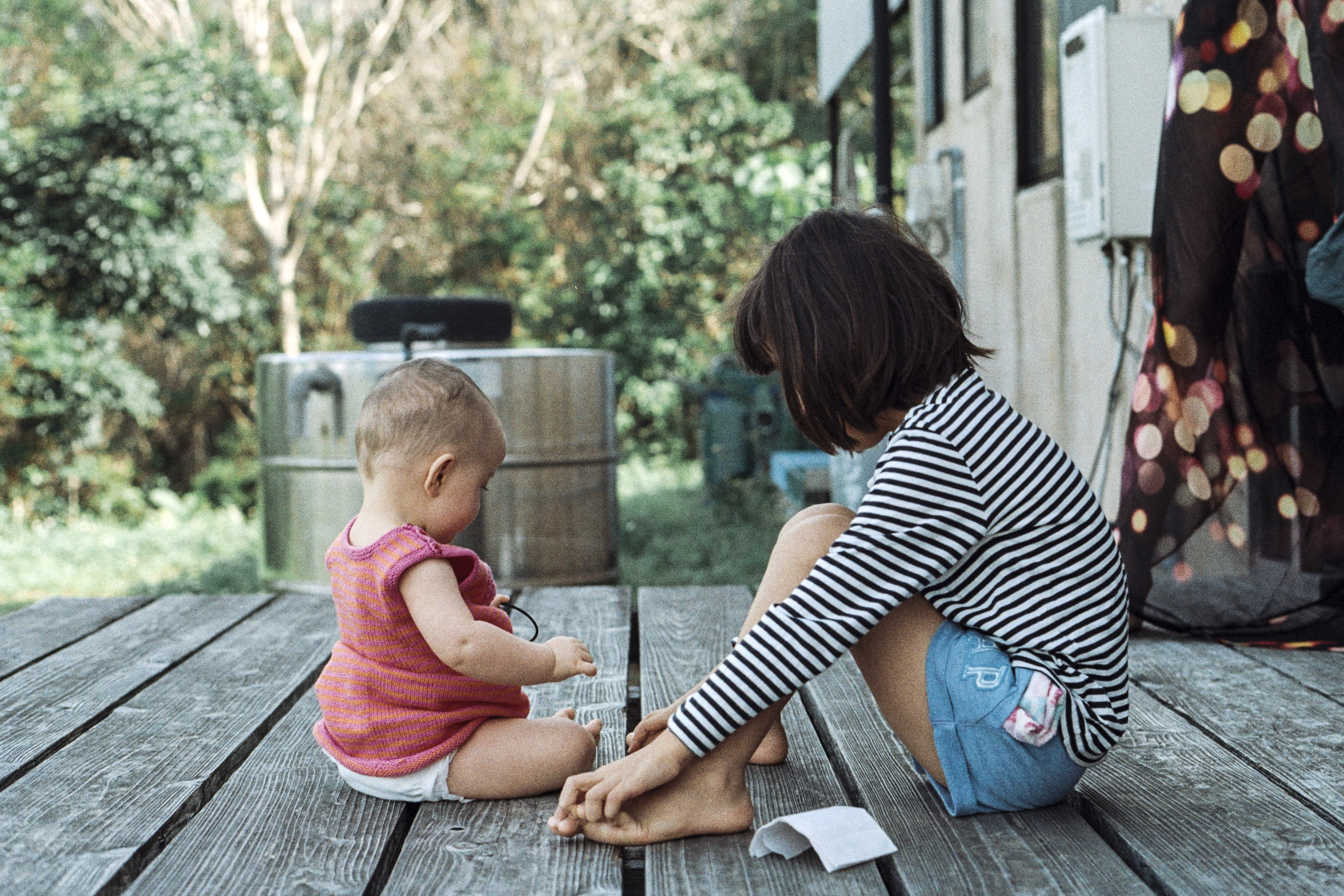 girl and toddler sits on gray wooden planks during daytime