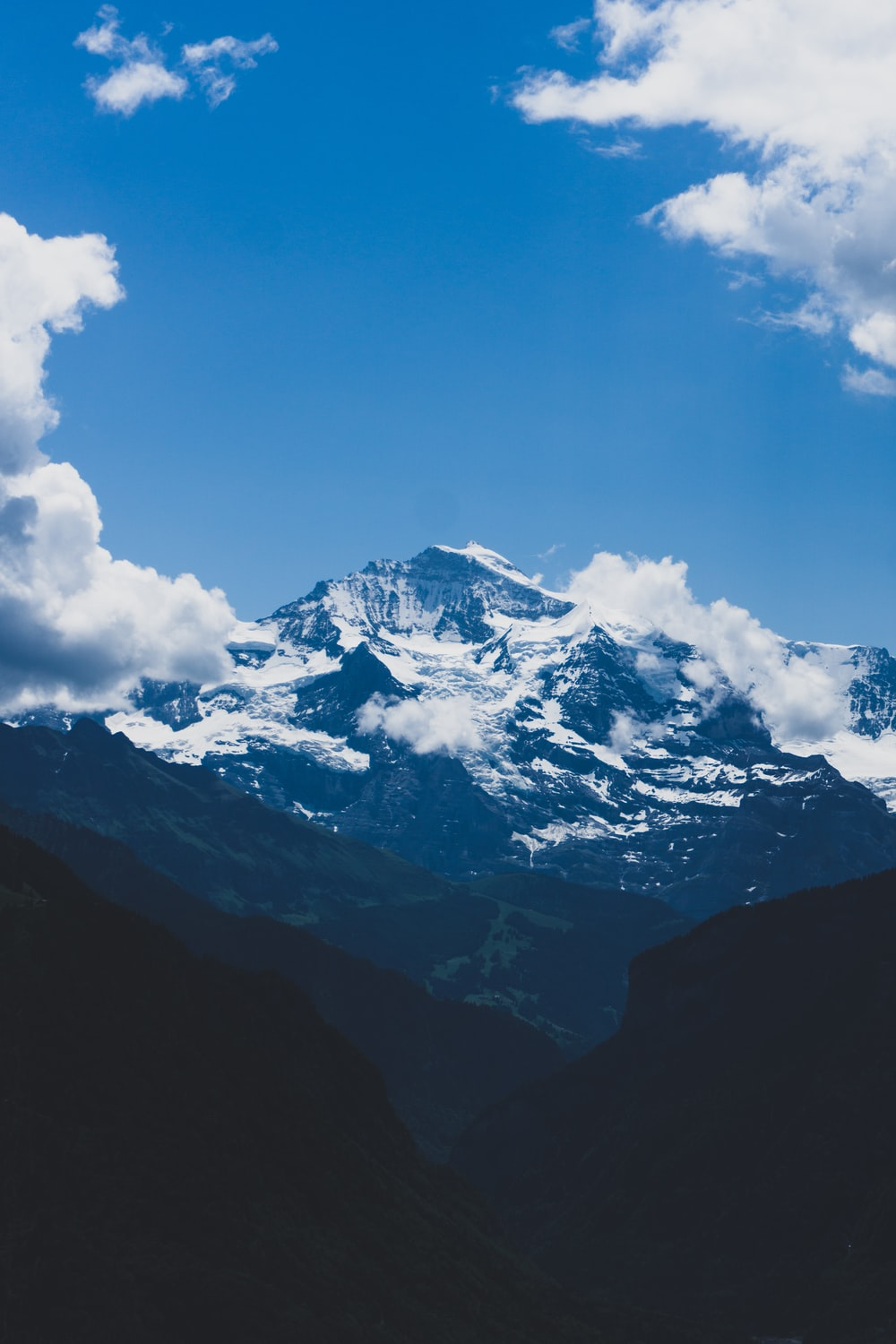 snow-covered mountain under white clouds during daytime