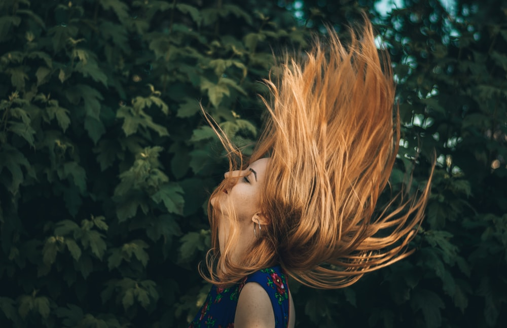 woman waving her hair beside green leafed plant