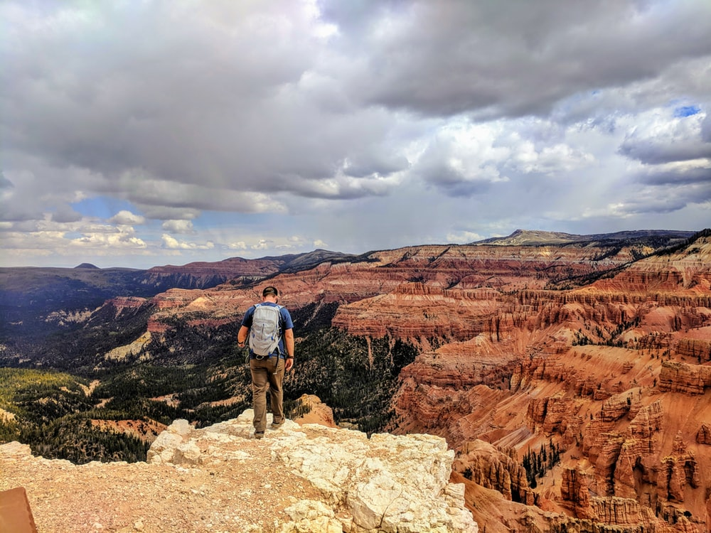 man standing at edge of a rock cliff