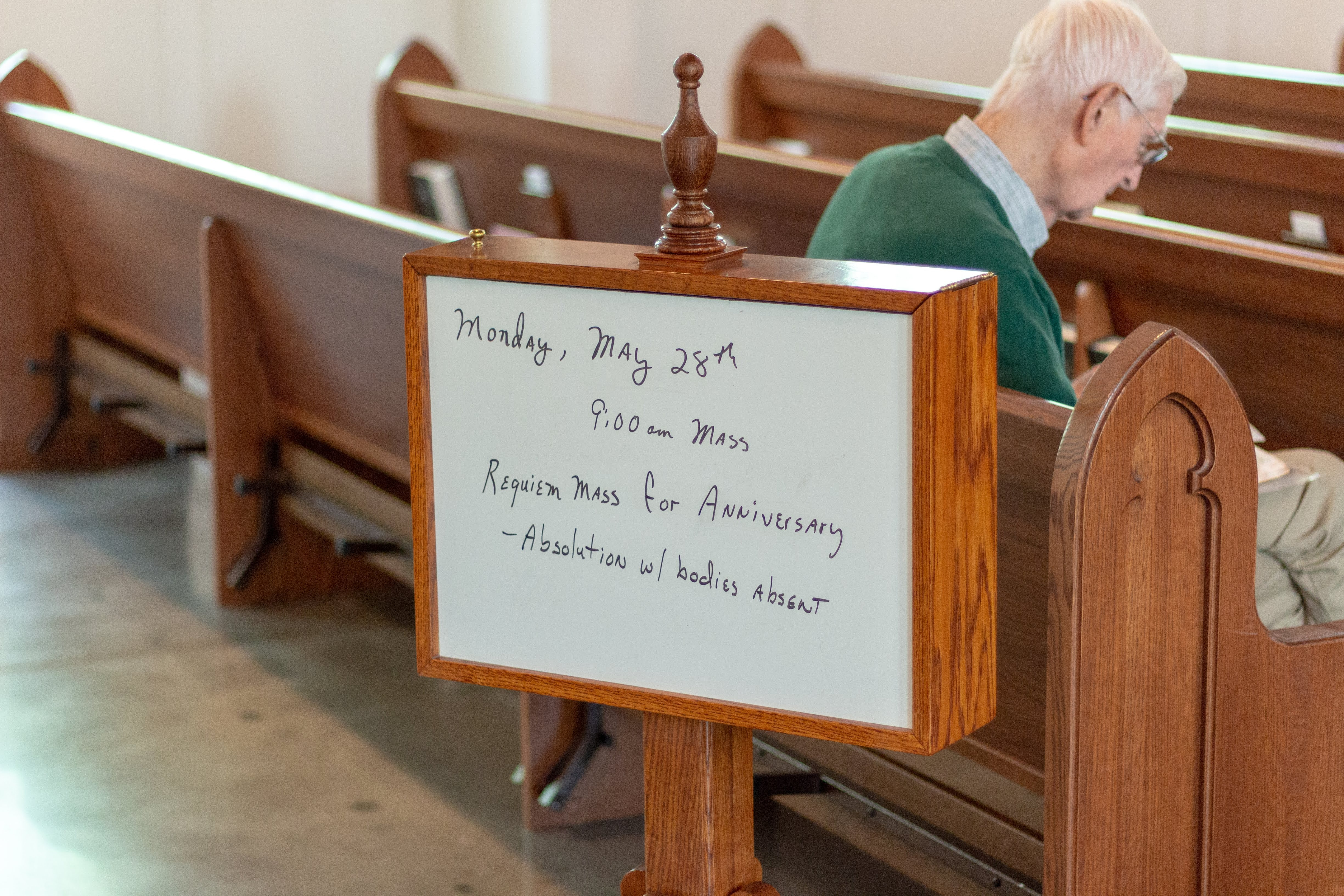man sitting on brown wooden church pew