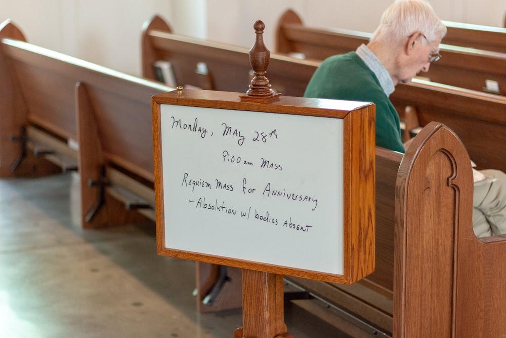 man sitting on brown wooden church pew